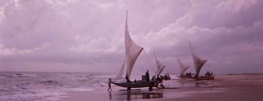Four jangadas on the beach next to the water, ready to go to sea.