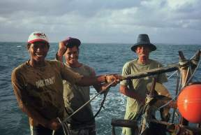 Three jangadeiros on a jangada. One of them is steering while the other two hold espeque lines.