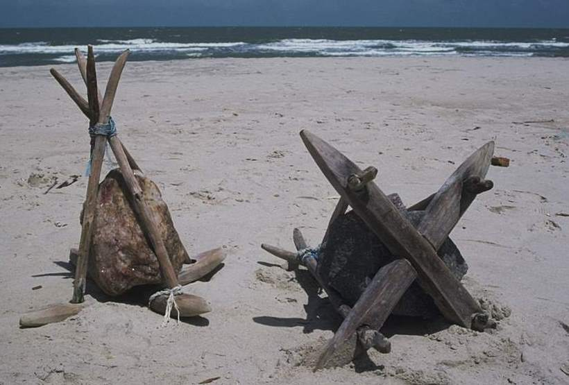 Two fateixas sitting on the sand. One turned over to see its bottom.