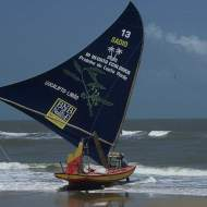 A jangada with a unique blue sail at the tide line, ready to leave.