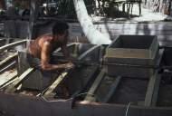 A carpenter building a Jangada de Tábuas (planked jangada)