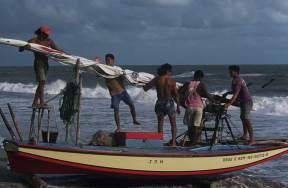 Jangadeiros standing on one of the larger jangadas preparing the mast to be raised.