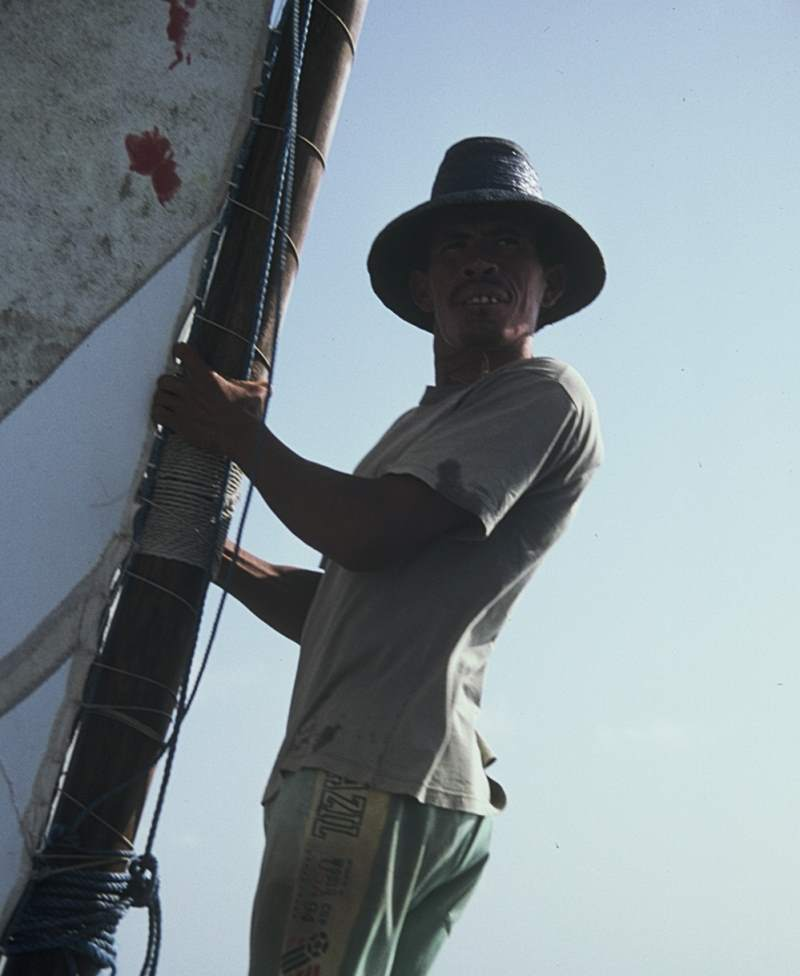 A jangadeiro holding the mast while looking out over the ocean.