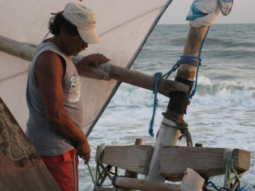 A jangada's boom being held in place by the peia. A jangadeiro with his hand on the boom.