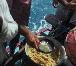 A jangadeiro is adding the caldo (fish broth) to the farinha to make the pirão