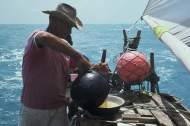 A jangadeiro is pouring broth from the cooking pot into a pan filed with farinha