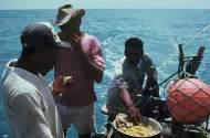 There jangadeiros eating fish and pirão while sailing.