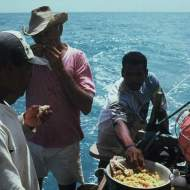 There jangadeiros eating fish and pirão while sailing.