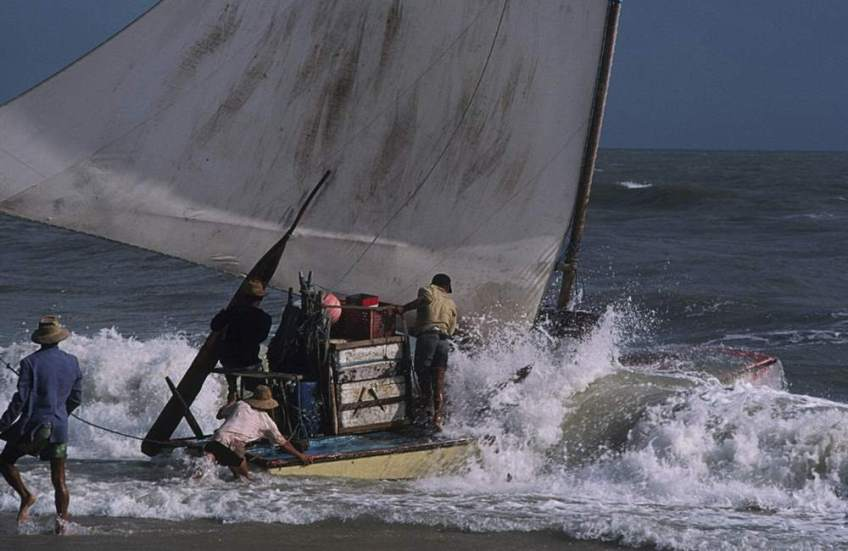 A jangada being pushed off as it leaves the beach.