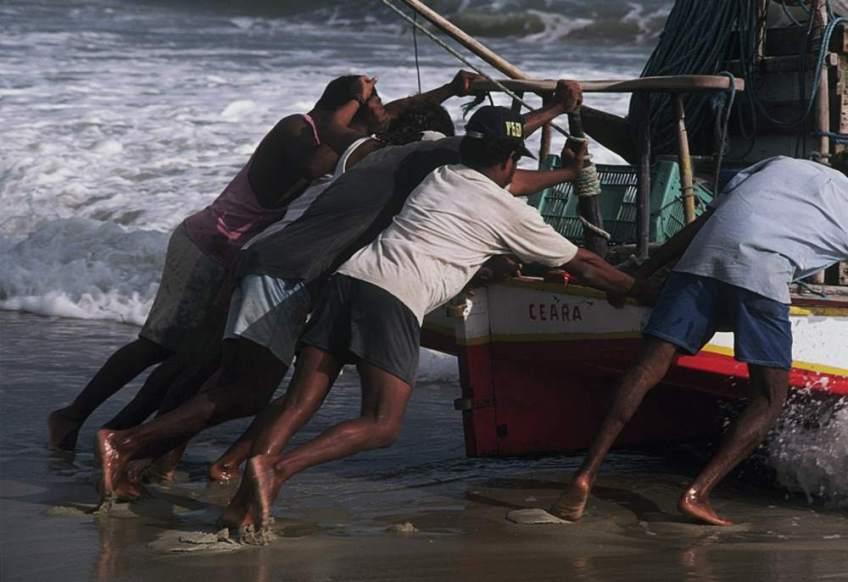 Roladores and Jangadeiros pushing a jangada into the water.
