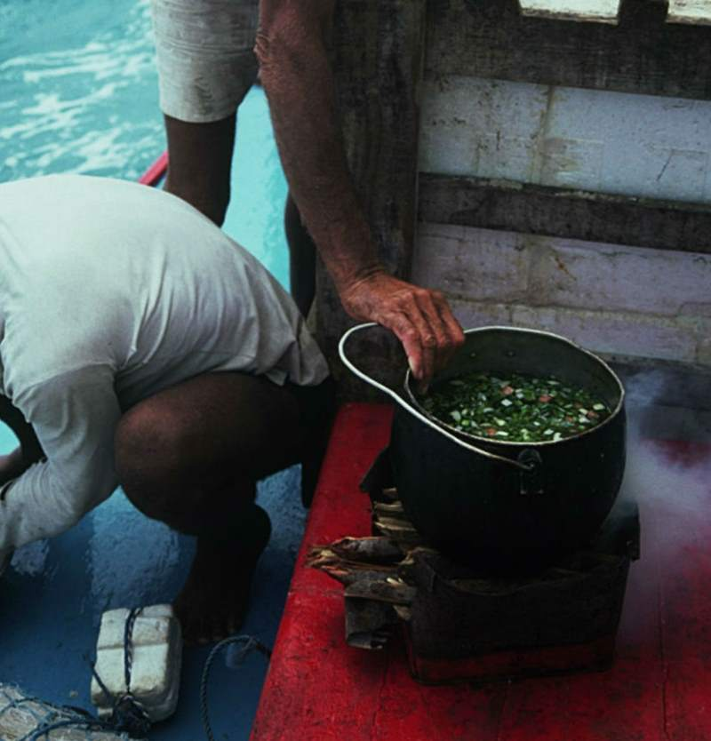 Jangadeiro setting the fish stew pot on the fire.