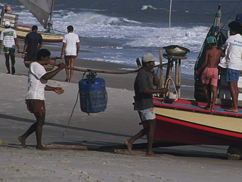 Two men carrying a jangada's Barril or water cask.