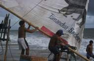 Two jangadeiros running the boom out to set the sail.