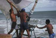 Two jangadeiros placing the boom head on the mast.