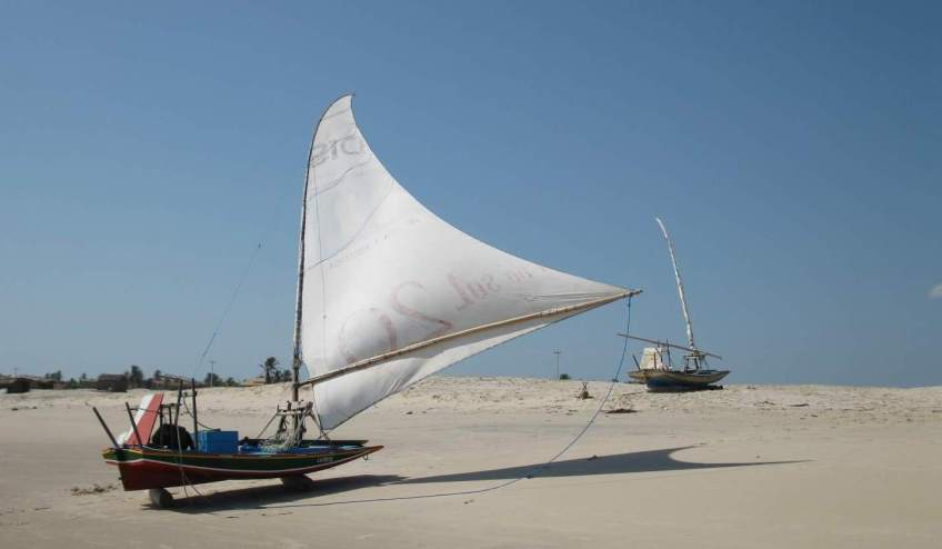 A paquete on the beach with its sail up to dry out in the wind.