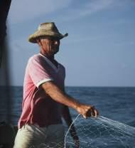 A jangadeiro pulling in a fishing net.