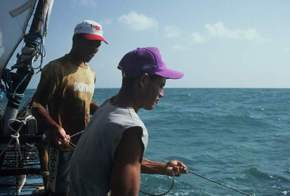 Two jangadeiros pulling up a lobster pot.