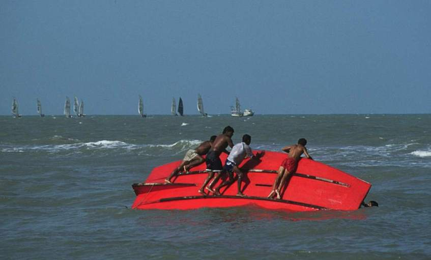 An overturned jangada in the surf, its red bottom up, several people on the hull trying to flip it over.