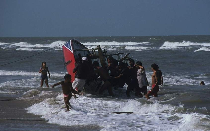 A jangada on it's side in the surf, being righted by a group of people.
