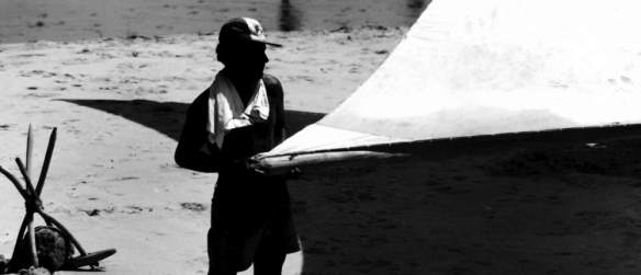 A jangadeiro working on the mainsail.