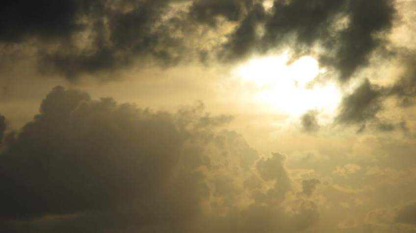 Sky with sun filtering through clouds.