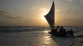 Fishermen pushing a jangada into the sea at sunrise.