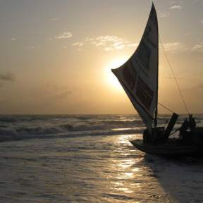 Fishermen pushing a jangada into the sea at sunrise.