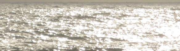 Closeup of the ocean, back-lit by the sun.