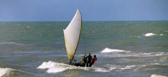 Two men on a jangada, sailing through whitecaps.