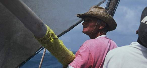 A jangadeiro removing the boom from the mast.
