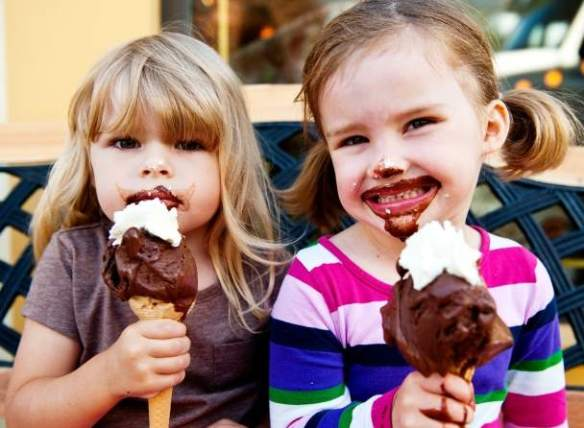 Two young girls eating gelato cones.
