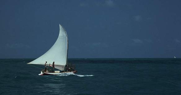 Jangada sailing by with lobster traps. Jangadeiros waving.