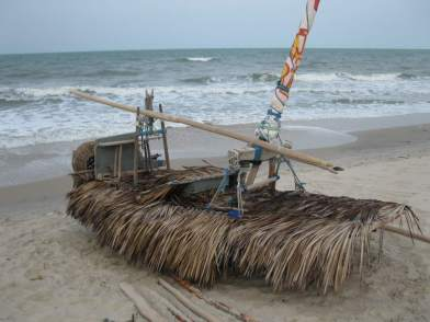 A jangada on the beach, its deck covered with palm fronds to protect against the hot sun.